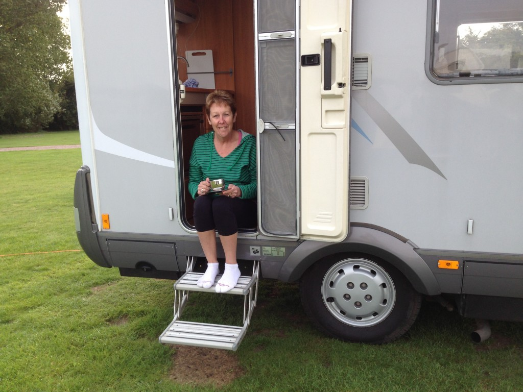 Pam enjoys a morning coffee on the step of our Hymer, Cambridge, UK.  2013